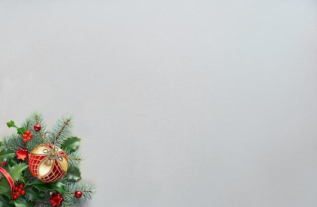 Natale con composizione ad angolo - pallina con ornamenti dorati, bastoncini di zucchero a strisce su ramoscelli di agrifoglio e abete. layout piatto in verde e rosso su carta grigio argento, copia-spazio.