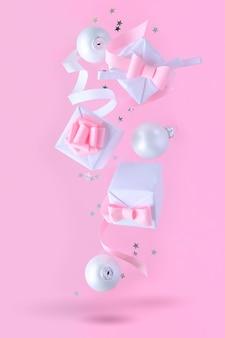 Natale con decorazioni e scatole regalo su sfondo rosa
