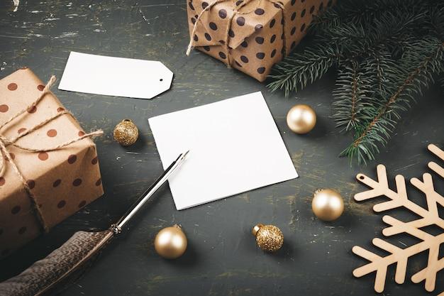Natale con lettera, busta e penna piuma circondato da decorazioni stagionali