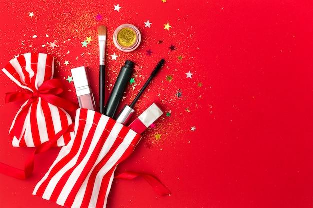 Natale con mascara, rossetto e ombre. composizione piatta con scintillii, sacchetti regalo e prodotti cosmetici per la festa di capodanno.