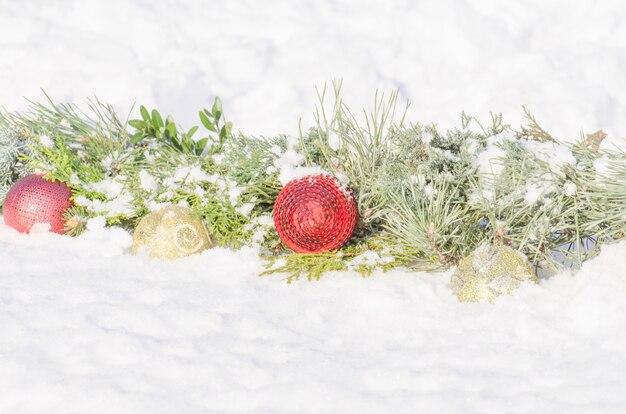 Natale con rami di abete, ornamenti su neve bianca