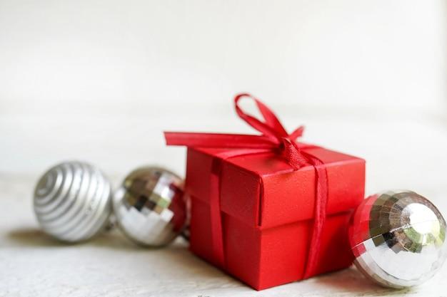 Natale con regalo rosso, palle di capodanno su bianco. disteso, copia spazio