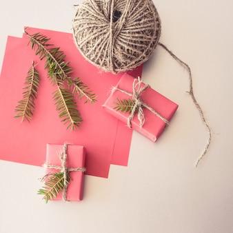 Natale con scatole regalo, bugne di corda, carta e decorazioni sul rosso. incartamento di regalo .