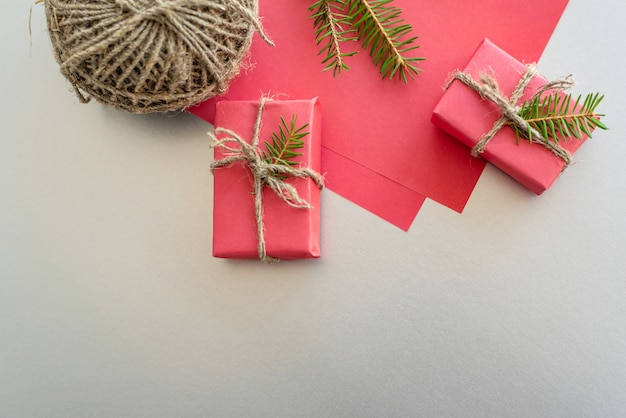 Natale con scatole regalo, bugne di corda, carta e decorazioni sul rosso. preparazione per le vacanze.