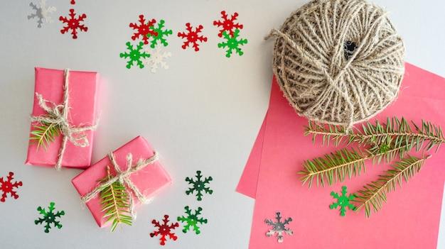 Natale con scatole regalo, corda, decorazioni di carta sul rosso. preparazione per le vacanze. incartamento di regalo .