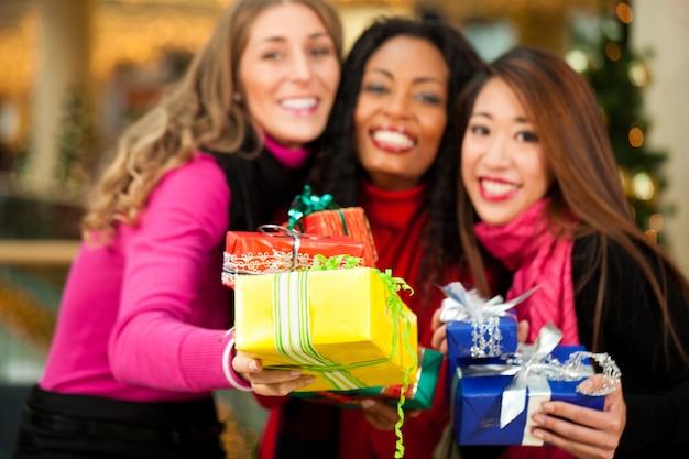 Natale degli amici che compera con i presente in centro commerciale