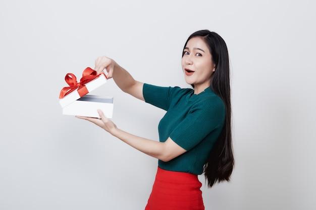 Natale del contenitore di regalo della tenuta della donna su bianco