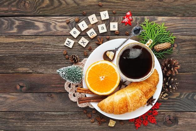 Natale e capodanno 2017 con colazione continentale tazza di caffè caldo con cannella, arancia fresca e cornetto. decorazioni: fiocco di neve, tovagliolo all'uncinetto, pigne.