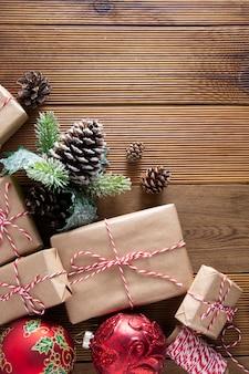 Natale e vacanze invernali sfondo. cchristmas confezione regalo con pigne, rami di abete, sul tavolo di legno marrone con spazio di copia. natale piatto disteso, copia spazio.