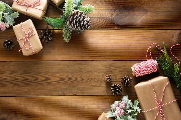 Natale e vacanze invernali sfondo. cchristmas confezione regalo con pigne, rami di abete, sul tavolo di legno marrone con spazio di copia. natale piatto disteso.