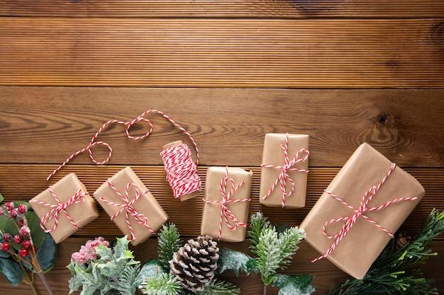 Natale e vacanze invernali sfondo. contenitore di regalo di natale con pigne, rami di abete, sul tavolo di legno marrone con spazio di copia. natale piatto disteso, copia spazio.