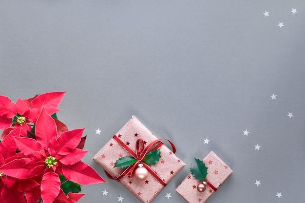 Natale festivo con scatole regalo rosa incartate decorate con bigiotteria e foglia di agrifoglio.