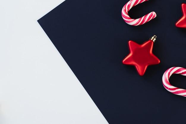 Natale geometrico disteso su sfondo colorato alla moda. sfondo creativo. bastoncino di zucchero, decorazione dell'albero di natale stella rossa e rami di abete