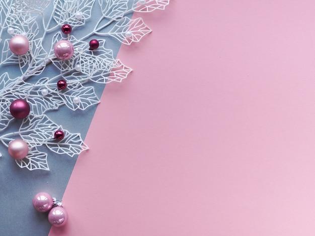 Natale inverno piatto giaceva in due colori di carta, rosa e argento, sfondo con copia-spazio. ramoscelli invernali bianchi con foglie geometriche lucide e gingilli di natale in vetro sparsi, rosa e magenta.
