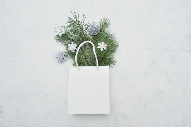 Natale mock up flat lay con pacchetto bianco e abete e fiocchi di neve