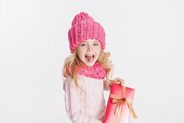 Natale. nuovo anno. bambina che tiene presente in abiti invernali. cappello e sciarpa rosa. inverno