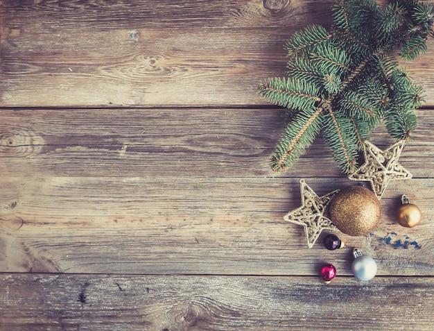 Natale o capodanno in legno rustico con decorazioni giocattolo e ramo di un albero di pelliccia, vista dall'alto