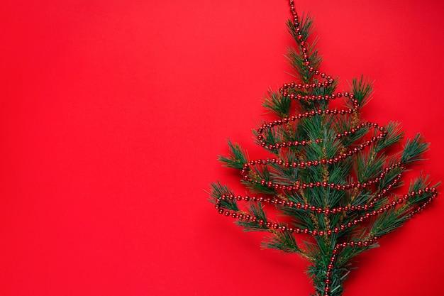 Natale o ornamenti natalizi: rami di un albero di natale sotto forma di albero di natale con perline rosse su fondo rosso con copyspace