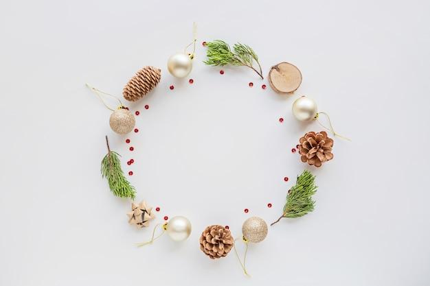 Natale piatto disteso con palline, rami di abete su bianco