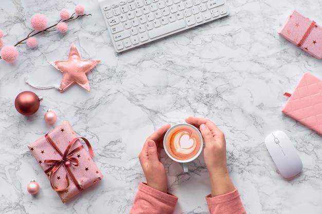 Natale piatto disteso sul tavolo di marmo. mani che si scaldano dalla calda tazza di caffè latte a forma di cuore. decorazioni invernali: ramoscelli di abete, stelle e ninnoli rosa, copia-spazio