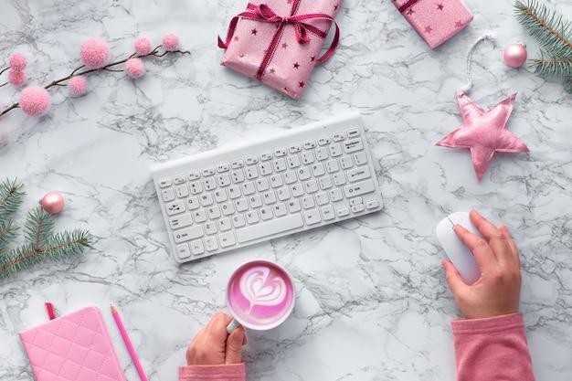 Natale piatto giaceva sul tavolo di marmo, area di lavoro festiva con tastiera del computer. mani che tengono topo e tazza del latte delle barbabietole. decorazioni invernali: ramoscelli di abete, stelle e ninnoli rosa.