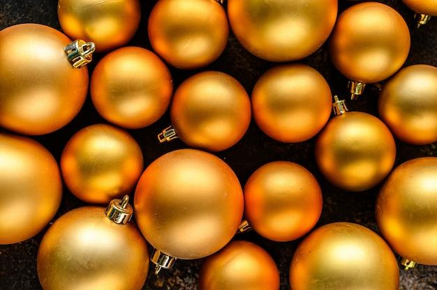 Natale piatto lay, anno nuovo sfondo. bagattelle d'oro su sfondo scuro.