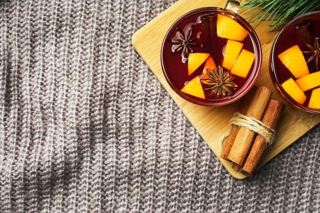 Natale vin brulè con spezie e frutta su una coperta a maglia.