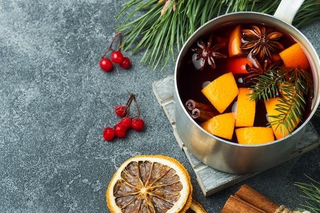 Natale vin brulè con spezie e frutta sul tavolo.