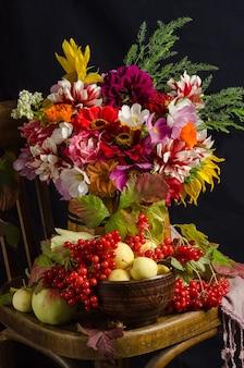 Natura morta atmosferica autunnale con un bellissimo bouquet colorato di fiori da giardino, bacche rosse, mele, foglie autunnali su una superficie nera.