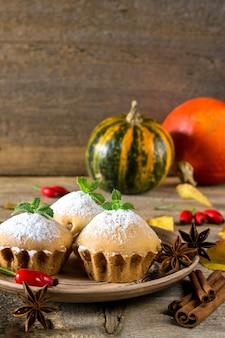 Natura morta autunnale. cupcakes fatti in casa con zucchero a velo con bastoncini di cannella, stelle di anice, zucche, bacche di cinorrodo e foglie di autunno su superficie di legno rustica