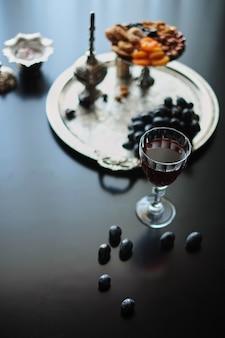 Natura morta bicchiere di vino e frutta secca sfondo nero