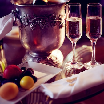 Natura morta, cena romantica, due bicchieri e champagne nel secchiello del ghiaccio. celebrazione o festività