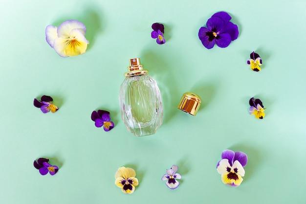 Natura morta, composizione, set con bellissimi fiori freschi colorati, fragrante e bottiglia con profumo femminile. viole. vista dall'alto. disteso.