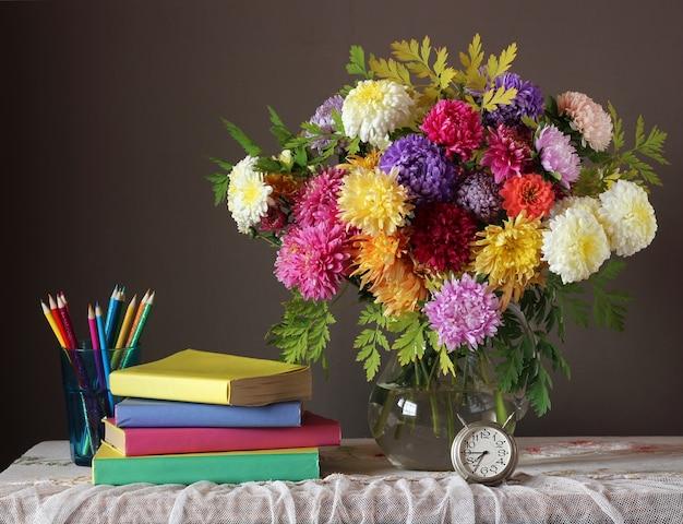 Natura morta con bouquet autunnale e libri.