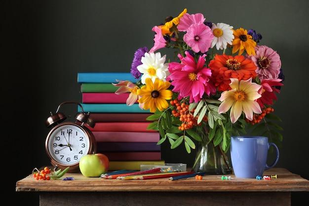 Natura morta con bouquet autunnale, sveglia e libri. formazione scolastica.