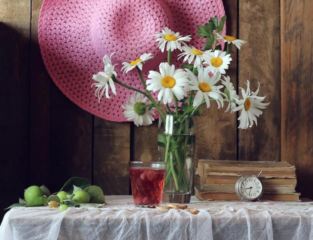 Natura morta con bouquet di margherite, libri, mele verdi, una sveglia, un cappello estivo e un bicchiere di composta.