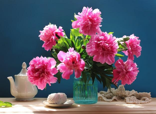 Natura morta con bouquet di peonie rosa e marshmallows. fiori dal giardino in un vaso di vetro blu.
