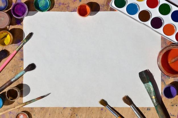 Natura morta con carta bianca, pennelli e barattoli di acquerello e pittura a guazzo