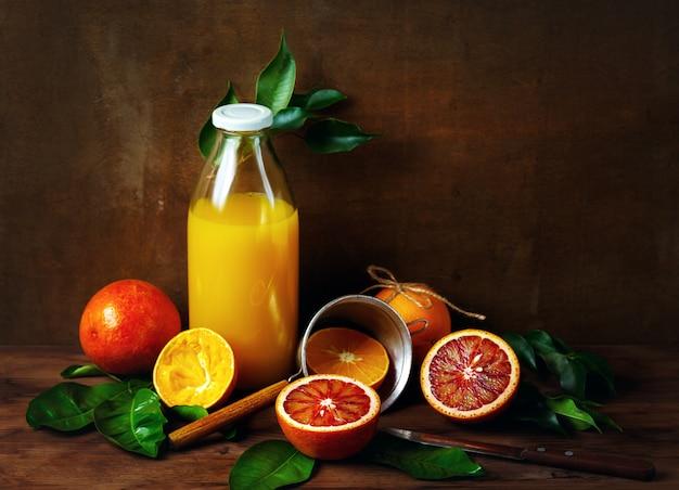 Natura morta con frutta e succo d'arancia in bottiglia