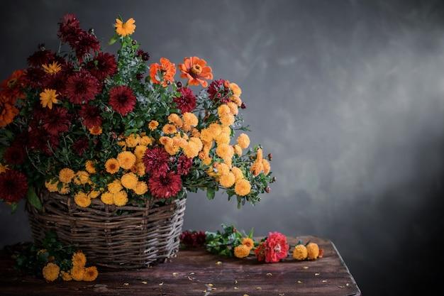 Natura morta con la merce nel carrello dei crisantemi sullo scaffale di legno