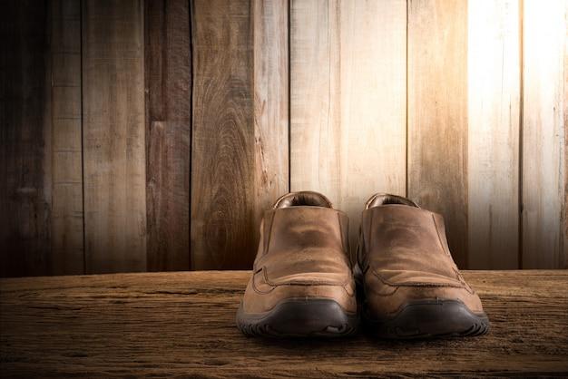 Natura morta con le scarpe degli uomini sul ripiano del tavolo di legno contro la parete del grunge