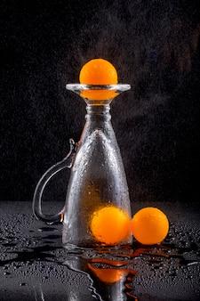 Natura morta con palline arancioni e un bicchiere di vetro sotto l'irrigazione a goccia con acqua