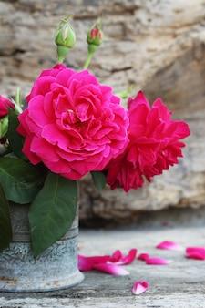 Natura morta con rose rosa fiore in vaso d'argento sullo spazio di legno del grunge