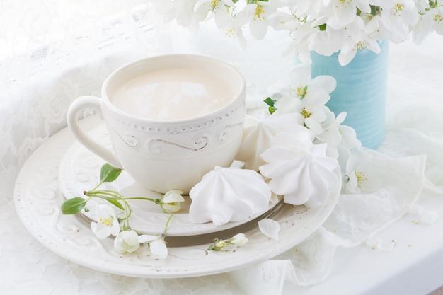 Natura morta con tazza di tè e ramo di fiori