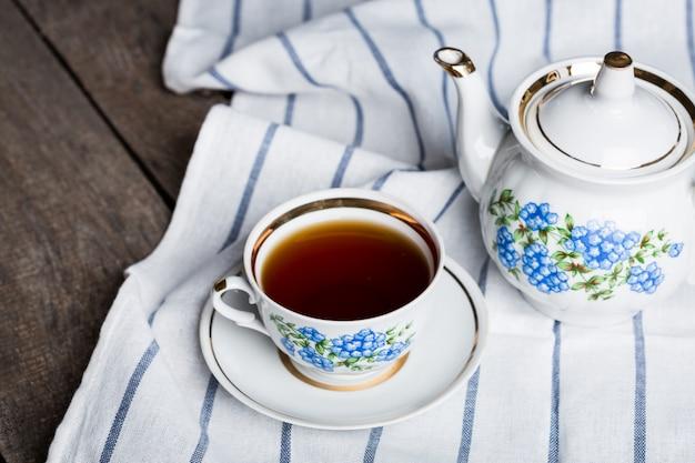 Natura morta con tazza di tè e tovaglia sul tavolo di legno