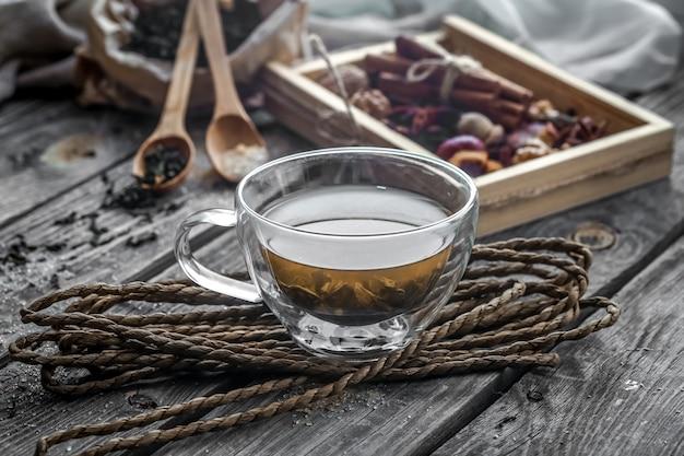 Natura morta con trasparente e fragrante tazza di tè allo zenzero su fondo in legno