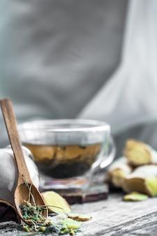 Natura morta con trasparente tazza di tè su fondo in legno
