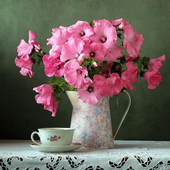 Natura morta con un bouquet nella brocca retrò e tazza sul tavolo