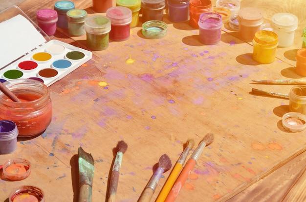 Natura morta con un sacco di pennelli e barattoli di pittura ad acquerello e tempera