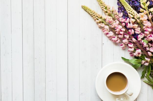 Natura morta con una ciambella della tazza di caffè e del lupino su una tavola di legno leggera.